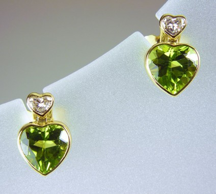 Peridot & diamond earrings in 18ct gold - Peridot & diamond heart earrings in 18ct yellow gold. 2.53ct peridot and 0.19ct diamond heart shaped pairs, bezel set as stud earrings 7 x 11mm.