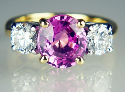 Pink sapphire & diamond ring in 18ct white & yellow gold - 2.72ct pink sapphire set with a 1.02ct matched pair of 0.51ct G colour VS2 clarity round brilliant cut diamonds in 18ct white and yellow gold.  This ring was created using the solitaire diamond and shank of the customer's original engagement ring and was to mark a significant wedding anniversary.    Just Gems is expert at remodelling jewellery, reusing original gems and gold, and making something truly splendid to celebrate the major milestones in life!