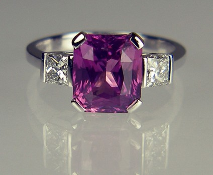 Pink Sapphire & Diamond Ring - 3.62ct pink sapphire set with a 0.46ct pair of princess cut diamonds in F colour SI clarity in 18ct white gold