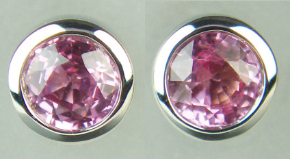 Pink sapphire earstuds in 9ct white gold - 5.1mm round pink sapphire earstuds in rubover white gold setting. The pair of pink sapphire rounds weigh 0.60ct.