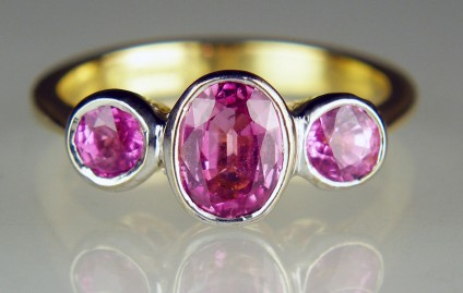 Pink sapphire 3 stone ring - Faceted pink sapphire three stone ring with a central 7 x 5mm oval flanked by a pair of 4mm rounds totalling 1.65ct, and rubover set in 18ct yellow and white gold