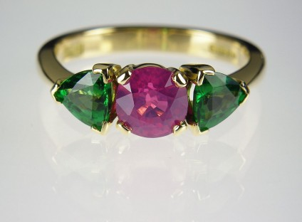 Pink sapphire & tsavorite ring - Vivid pink sapphire 1.17ct flanked by a 0.97ct pair of tsavorite garnet pear cuts in 18ct yellow gold. Centre stone 6mm diameter.