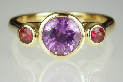 Red spinel & purple sapphire ring - 1.62ct round cut purple sapphire from Madagascar, set with a pair of 18pt red spinels in 18ct yellow gold