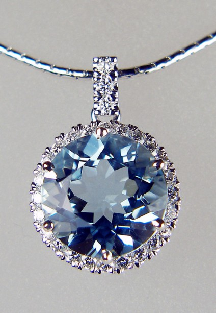 """Aquamarine & diamond cluster pendant - 11mm round aquamarine weighing 4.17ct and surrounded by 0.39ct of round brilliant cut diamonds in F colour VS clarity, mounted as a pendnat in 18ct white gold and suspended from a 16"""" anaconda style chain"""