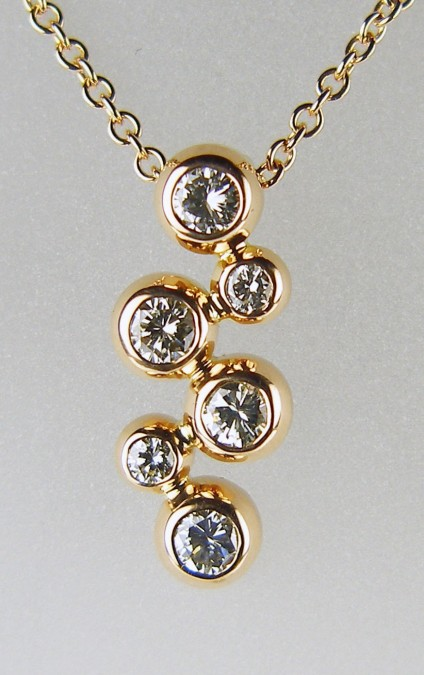 "Rubover set diamond pendant in 18ct rose gold - Pendant of 6 rubover set diamonds, 4 x 20pt and 2 x 2.7mm, mounted in 18ct rose gold suspended from a 16-18"" adjustable 18ct rose gold trace chain. The diamond grade is G/H colour and SI clarity. Total diamond weight is 0.97ct."