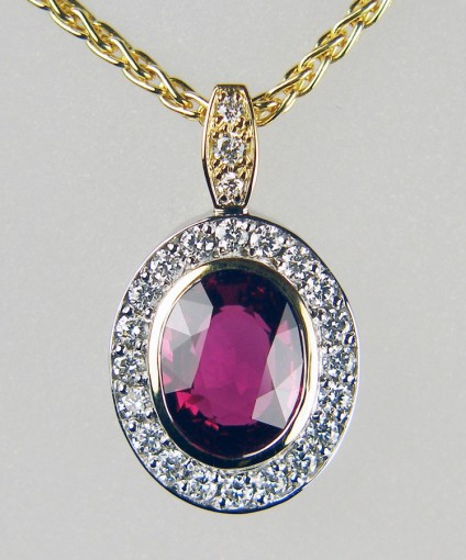 "Ruby & diamond pendant - Pendant in 18ct yellow and white gold, set with a central 2.18ct oval faceted natural unheated ruby accompanied by GRS report GRS2015-037034 dated 6th March 2015.   The ruby is surrounded by a halo of 20 pavé set 1.5mm round brilliant cut diamonds in F colour VS clarity. The pendant is suspended from a bail set with a single 1.5mm round diamond and 2 x 1.2mm round diamonds of the same quality.  Total diamond weight 0.28ct.  The pendant is suspended from an 18ct yellow gold chain 16-19"" adjustable."