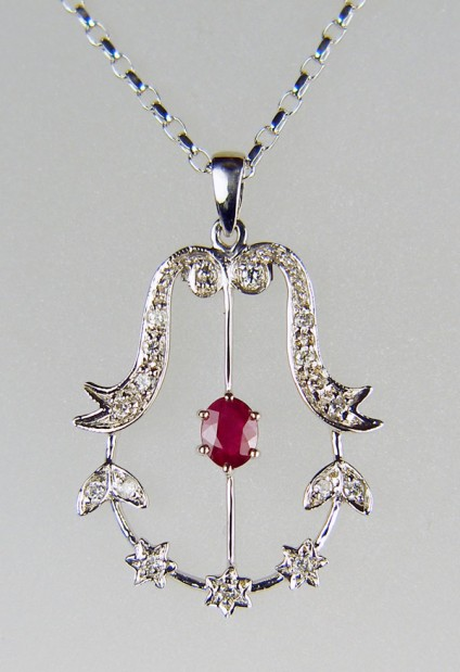 "Ruby & diamond pendant in 9ct white gold - 0.5ct oval faceted ruby set with 0.2ct diamonds in 18ct white gold pendant. The piece is secondhand, measures 32mm long by 22mm wide and is in excellent condition. It is suspended from a 20"" 9ct white gold chain."