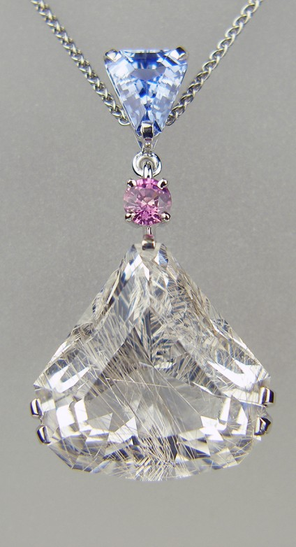 Rutilated quartz & sapphire pendant in 18ct white gold - Beautiful delicate silvery special cut 27.6ct rutilated quartz created by award winning lapidary Ivan Williamson of Hascosay Gems.  Also set with 2.08ct triangular cut natural blue sapphire and 0.42ct round cut natural pinkish purple sapphire. All mounted in 18ct white gold.