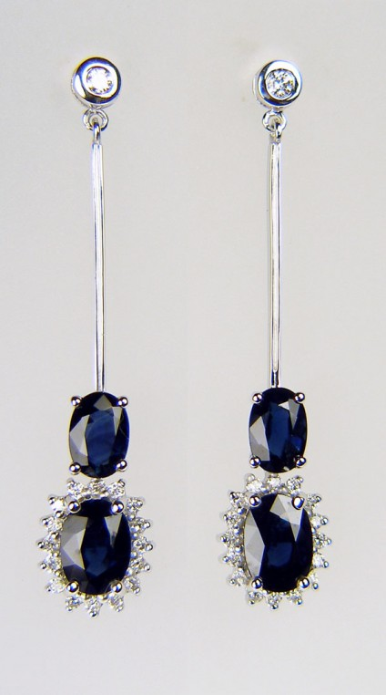 Sapphire & diamond earrings - Elegant drop sapphire & diamond earrings in 9ct white gold. Two matched oval sapphire pairs totalling 2.0ct and surrpunded by 30pts of round brilliant cut diamonds. The rubover set studs are set with a 15pt matched diamond round brilliant cut pair. The earrings are 40mm total length.