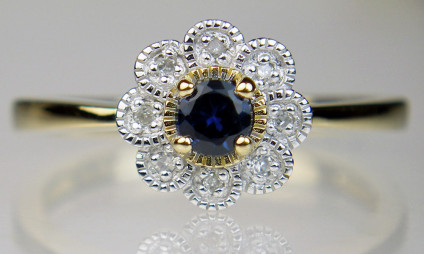Sapphire & diamond cluster ring in 9ct yellow gold - Little flower-like ring set with a dark sapphire round cut surrounded by a halo of tiny round brilliant cut with diamonds, in 9ct yellow gold