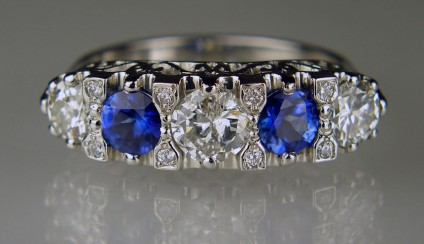 Engraved sapphire & diamond ring in platinum - 1.09ct of old cut round diamonds taken from a customer's remodelled 3 stone ring and reset with a further 0.06ct of tiny round brilliant cut diamonds and a 0.78ct round cut bright blue sapphire pair mounted in a handmade platinum engraved mount to replicate the popular late Victorian/early Edwardian setting style often seen in antique rings.