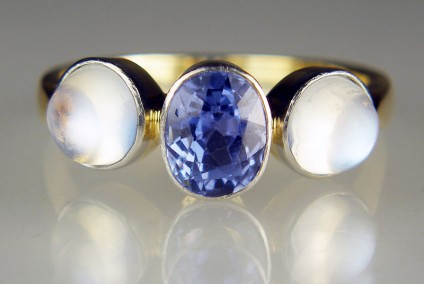 Sapphire & moonstone ring in yellow gold & platinum - Antique ring in 14ct yellow gold and platinum, set with a central oval faceted unheated natural sapphire in a pretty harebell blue and flanked by a matched pair of round cabochon moonstones. We estimate the sapphire to weigh approximately 1.5ct  (7.5 x 5.7 mm) and the moonstones almost 1ct each stone (6mm rounds). The stones are rubover set with a thin veneer of platinum to minimise visibility of the mount.  This is a very beautiful and unusual ring , finger size Q.