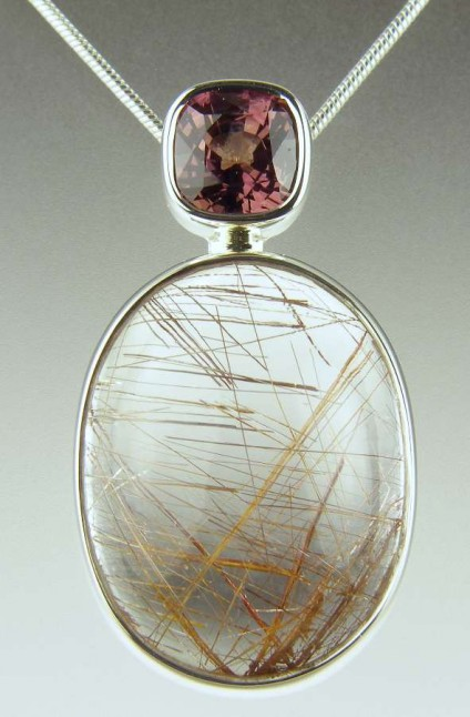 Rutilated quartz & brown sapphire pendant - 14.92ct oval cabochon of rutile included quartz (also know as Venus hair stone) set with a 1.5ct pinkish brown cushion cut sapphire as a pendant mounted in silver