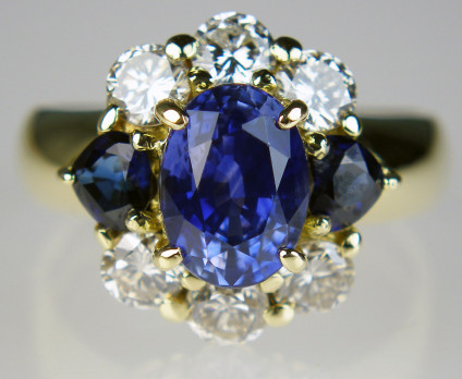 Sapphire & diamond cluster ring in 18ct yellow gold - Spectacular sapphire & diamond cluster ring in 18ct yellow gold. The central oval sapphire is 2.31ct and the matched flanking pair of darker trillion cut diamonds weigh 1.25ct, there are also 0.76ct of round brilliant cut diamonds top and bottom.