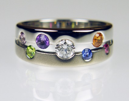 Sapphire & diamond ring in palladium - Round cut sapphires in assorted jewel colours shine out from the matt and shiny palladium mount, along with a round brilliant cut diamond. An exquisite and unique ring, mad to order for a client.