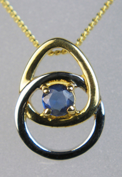 "Sapphire pendant in white & yellow gold - Delicate and modern pendant in 9ct white and yellow gold set with a round cut blue sapphire suspended from an 18"" 9ct yellow gold chain"