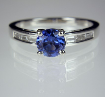 Sapphire & diamond ring in platinum - Round brilliant cut blue sapphire of lovely and intense periwinkle blue 0.9ct.  Set with 0.19ct baguette cut diamonds in platinum.