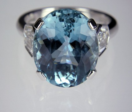 Aquamarine & Diamond Ring in 18ct Gold - Lady's 3 stone aquamarine & diamond ring consisting of a central, mid greenish-blue, oval cut Brazilian aquamarine of 7.59ct, flanked by a matched pair of G colour VS1 clarity, shield cut diamonds weighing 0.94ct in total in 18ct white gold.