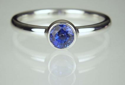 Sapphire Ring - 0.69ct round brilliant cut rich blue sapphire ring in delicate rubover setting in 18ct white gold