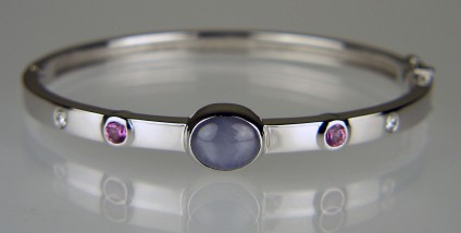 Star sapphire & diamond bangle - Elegant bangle in 18ct white gold set with a 4.36ct grey star sapphire set with 0.57ct of pink sapphires and 0.16ct of diamonds. This bangle was designed for the client, whose birthstone is sapphire, to wear daily and was a major birthday present to herself.  Just Gems has a wide selection of beautiful birthstone gems. We make many birthstone inspired pieces of special jewellery for our clients.