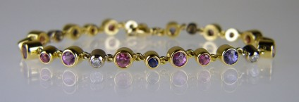 Sapphire & diamond bracelet in lilacs,blues and pinks - Lady's bracelet in 18ct yellow and white gold, set with 3.72ct of 4mm round sapphires in shades of lilac and pink; 0.45ct of 3mm round pink sapphires; 0.58ct of 3mm round blue sapphires and 0.45ct of 3mm round diamonds in F colour VS clarity. The sapphires are rubover set in yellow gold and the diamond rubover set in white gold.