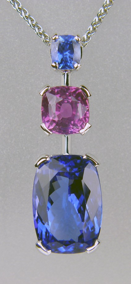 Tanzanite & sapphire pendant in 18ct white gold - 0.46ct rectangular cushion cut natural blue sapphire, set with 2.02ct square cushion cut natural vivid pink sapphire and 6.05ct rectangular cushion cut tanzanite, all set in 18ct white gold. The pendant is 29mm long and 9mm wide.