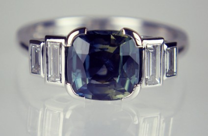 Teal sapphire & diamond ring in 18ct white gold - 1.88ct teal coloured cushion cut natural sapphire flanked by two pairs of baguette cut diamonds totalling 0.16ct and 0.10ct respectively.  The diamonds are graded as F colour VS clarity.