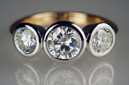Three stone diamond ring in platinum and rose gold - Lady's dress ring in 18ct rose gold & platinum with a 1.07ct round brilliant cut diamond, flanked by a 1.03ct pair of round brilliant cut diamonds (total diamond weight 2.10ct). The centre stone diamond grade is  I/I1, and the flanking stones I/I1 and H/SI2 respectively.  The diamonds are bezel set in platinum and the ring has a hallmarked 18ct rose gold shank.