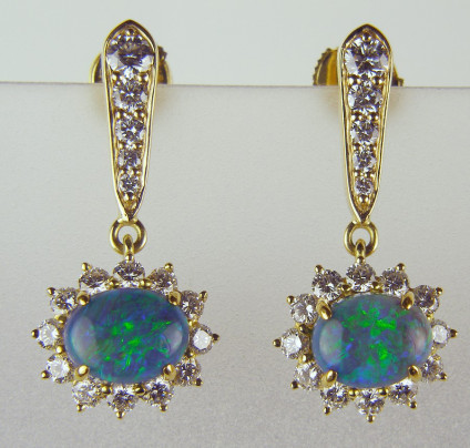 Black opal drop earrings in 18ct gold - Black opal cabochons surrounded by diamonds and suspended from a line of graduated diamonds, total diamond weight 1.50ct, diamond quality G colour VS clarity, all in 18ct yellow gold