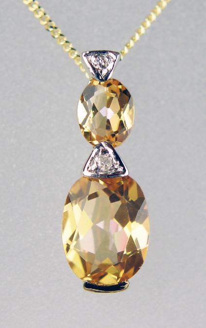 "Topaz & diamond pendant in 9ct yellow gold - Delicate oval topaz and white diamond pendant set in 9ct yellow gold and suspended from an 18"" 9ct yellow gold chain.Pendant is 16mm long"