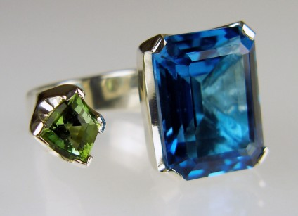 Tourmaline & blue topaz ring in silver - Between the finger ring made with customer's own 26.57ct emerald cut blue topaz and Just Gems shield cut green tourmaline, in silver.