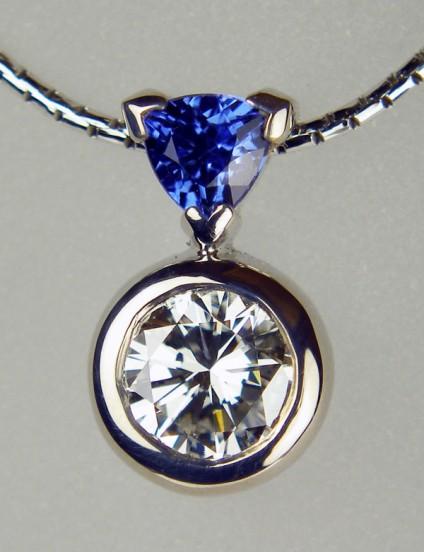 Diamond & sapphire pendant - 0.76ct round brilliant cut diamond in G colour SI1 clarity set with 0.31ct trillion cut sapphire in 18ct white gold