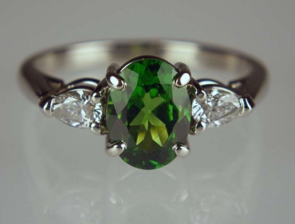 Agate - 1.49ct oval tsavorite garnet set with 0.28ct pair of pear cut diamonds in palladium