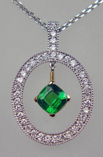 """Tsavorite & diamond pendant - 0.46ct cushion cut tsavorite garnet set in 18ct yellow gold and surround with a halo of 0.29ct round brilliant cut diamonds set in 18ct white gold. Suspended from a 16"""" fine trace chain."""
