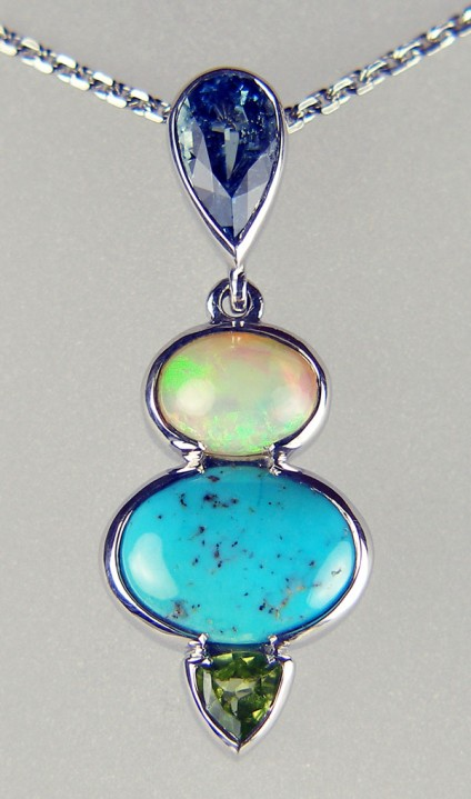 Aquamarine, turquoise, peridot, and opal birthstone pendant - Various gemstones (from the top - aquamarine, turquoise, opal and peridot) set in silver as a family birthstone (March, December, October, August) pendant